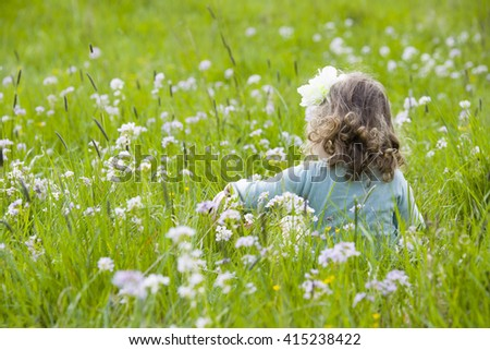 sweet little girl of two and a half years sitting on a colorful flower meadow and a flowering wreath in her hair, she picks flowers and has joy.