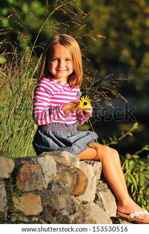 sweet little girl sitting on rocks in the park and holding a flower - stock photo