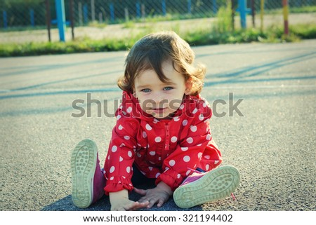 Sweet little girl sitting on the ground outdoor. Cute baby with curly hair looking at camera.
