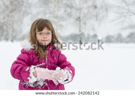 Sweet, little girl takes off her woolen gloves and looking at camera, winter landscape.Copy space - stock photo