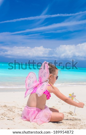Sweet little girl with butterfly wings on white beach - stock photo