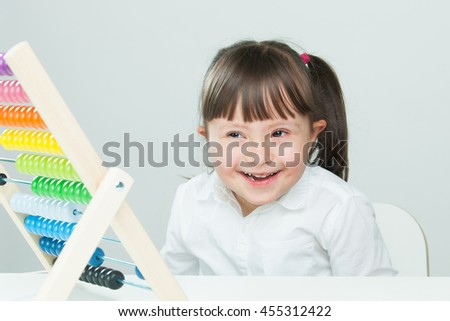 Sweet little girl with Down Syndrome, playing with wooden abacus