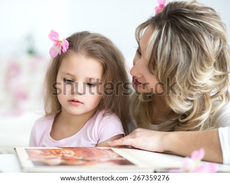 sweet little girl with mother reading book - stock photo