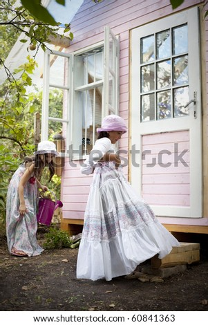 Sweet little girls in front of him little house for playtime - stock photo