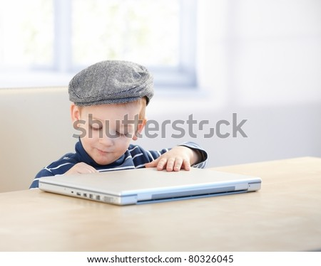 Sweet little kid sitting at table, wearing cap, playing with laptop.? - stock photo