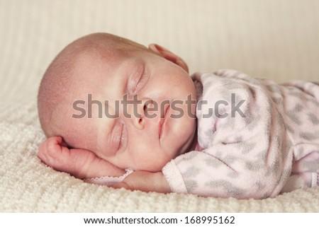 Sweet little newborn girl asleep at bedtime - stock photo