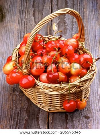 Sweet Maraschino Cherries in Wicker Basket on Rustic Wooden background - stock photo
