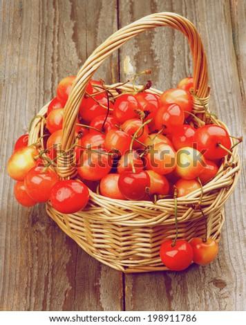 Sweet Maraschino Cherries in Wicker Basket on Wooden background. Retro Styled - stock photo
