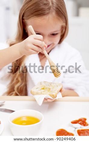 Sweet morning - little girl preparing to eat honey on bread, focus on the hand - stock photo