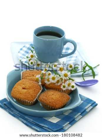sweet muffins on plate, cup of tea and chamomile isolated on white