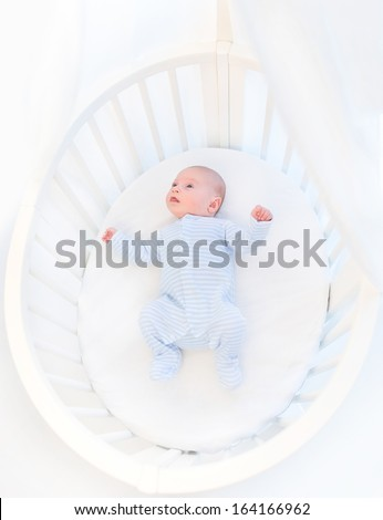 Sweet newborn baby boy in a white round crib with canopy - stock photo
