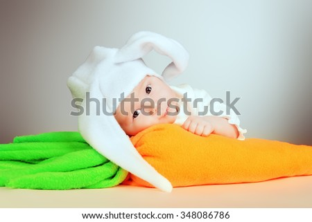 Sweet newborn baby in a white bunny costume.