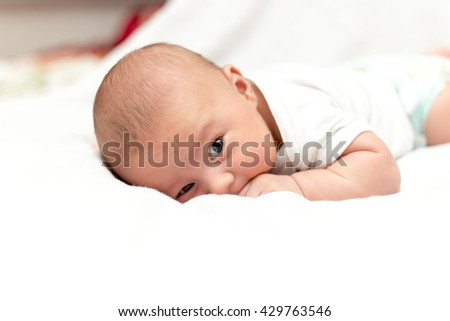 Sweet newborn baby lying peacefully while snuggled in warm white blankets