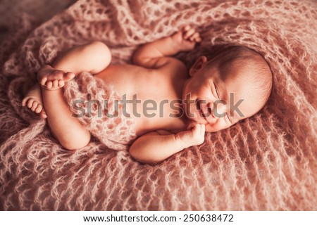Sweet newborn baby sleeping on knitted blanket - stock photo
