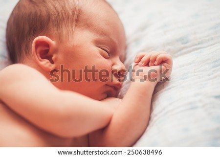 Sweet newborn baby sleeping on white blanket closeup - stock photo
