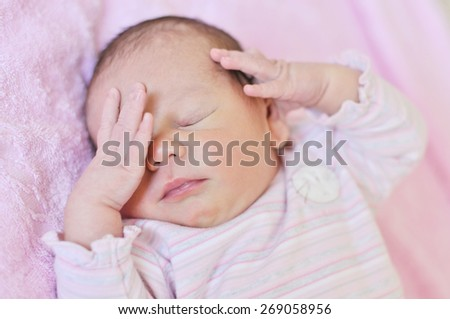 sweet newborn is sleeping with hands near the face - stock photo