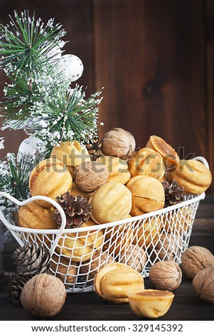 Sweet nuts and cones in a metal basket with white Christmas decoration, selective focus - stock photo