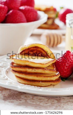 Sweet pancakes with honey and strawberry, selective focus