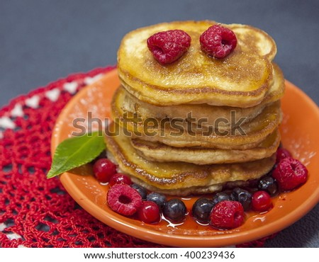 Sweet Pancakes with honey, strawberry, blueberry on plate and knitted cloth, photo