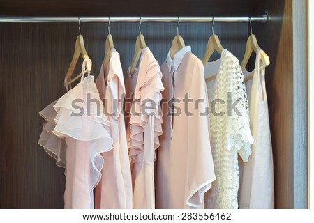 Sweet pastel blouses are hanging in open wooden wardrobe - stock photo