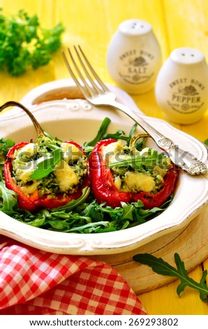 Sweet pepper stuffed with rice,spinach and cheese garnished with arugula leaves. - stock photo