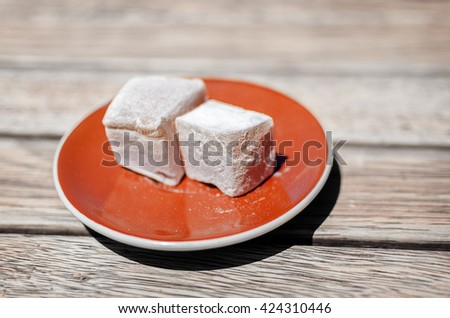Sweet pieces of turkish delight(lokum) confection on brown saucer. Soft selective focus and shallow depth of field - stock photo