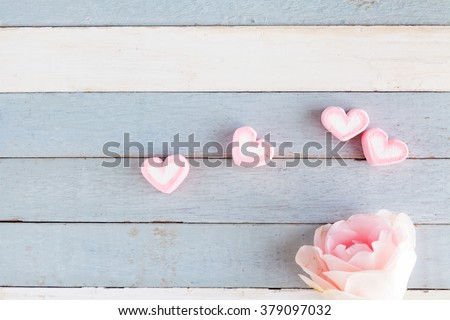 sweet pink heart marshmallow with pink rose on light blue vintage wood background