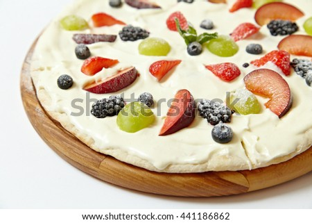 Sweet pizza with fruits and berries on white background - stock photo