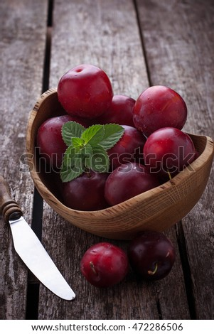Sweet plums on wooden background. Selective focus