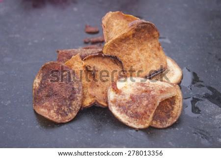 Sweet potato and potato chips, on a stone plate - stock photo