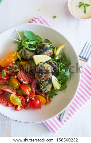 Sweet potato and spinach balls with tomato salad and rocket - stock photo