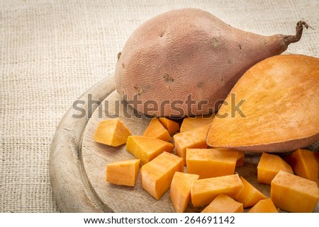 sweet potato cut and diced on a cutting board - stock photo
