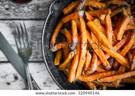 Sweet potato fries in cast iron skillet on wooden background - stock photo