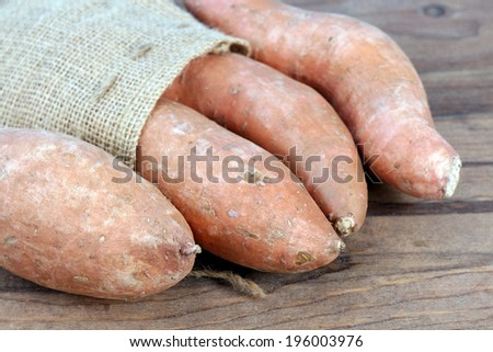 sweet potato on rustic table at market place - stock photo