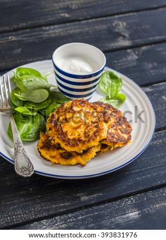 Sweet potato pancakes and fresh spinach on a dark wooden background - stock photo
