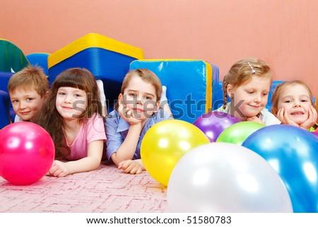 Sweet preschool children lying on floor among balloons - stock photo