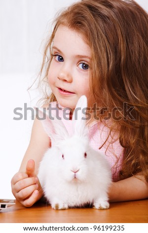 Sweet preschool girl and white rabbit - stock photo