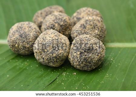 Sweet rice balls, popular traditional tea time snack of Kerala India made of flour, coconut and jaggery on Onam, Vishu, Ramadan festivals. South Indian food. - stock photo