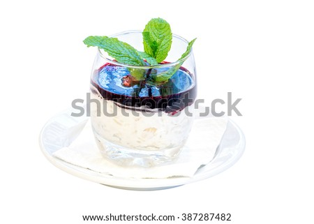 sweet rice cream desert with raspberry sauce and mint on white background
