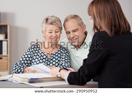 Sweet Senior Couple Listening to a Female Mortgage Agent Explaining to them Inside the Office. - stock photo