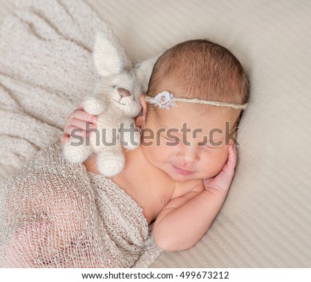 sweet sleeping infant girl with headband and toy in hand covered with warm shawl