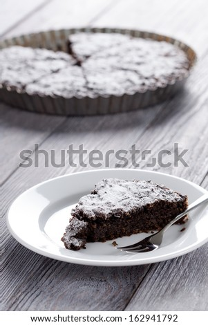 Sweet slice of brownie and whole cake in background. Homemade dessert decorated with sugar powder.