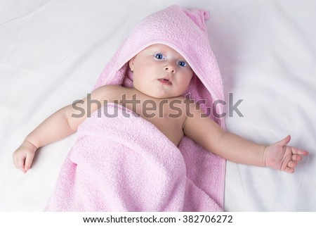Sweet small baby blue eyes covered with arose  towel - stock photo