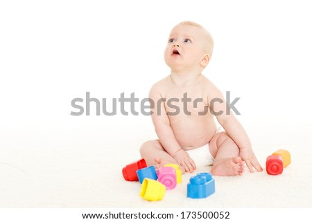 Sweet small baby with toys on a white background.