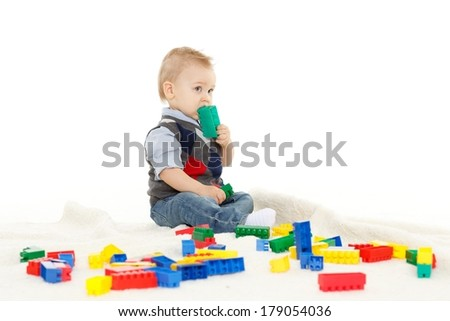 Sweet small boy  with toys on a white background.