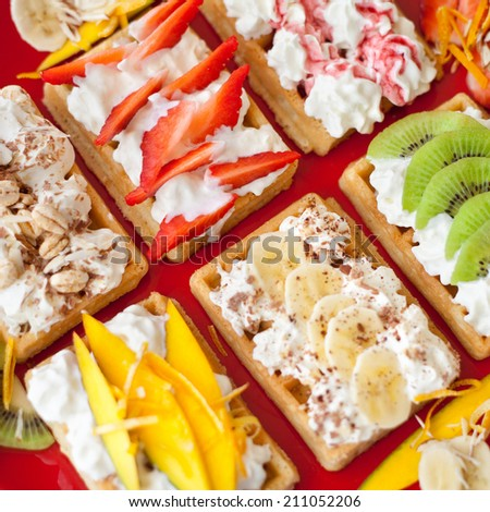 Sweet small waffles with whipped cream and different fruit fillings like strawberry, kiwi, banana, mango and chocolate topping. All prepared on red plate. - stock photo