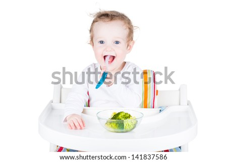 Sweet smiling baby eating broccoli, isolated on white