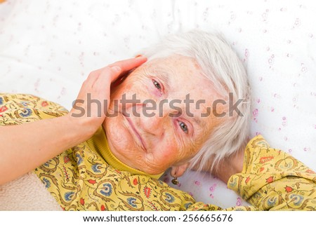 Sweet smiling elderly woman resting in bed - stock photo