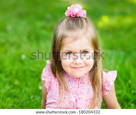 Sweet smiling little girl with long blond hair, sitting on grass in summer park, closeup outdoor portrait - stock photo