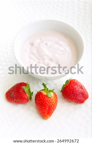 Sweet strawberry berries served with fresh organic yoghurt in a white bowl on a white plate. Fresh fruit dessert for the breakfast - stock photo